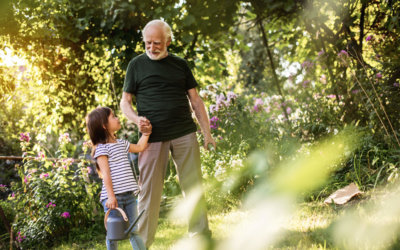 Smiling man with silver hair holding hand of pretty little girl. They talking while going to water flowers