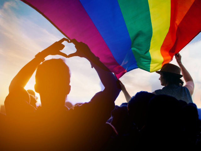 Pride community at a parade with hands raised and the LGBT flag.